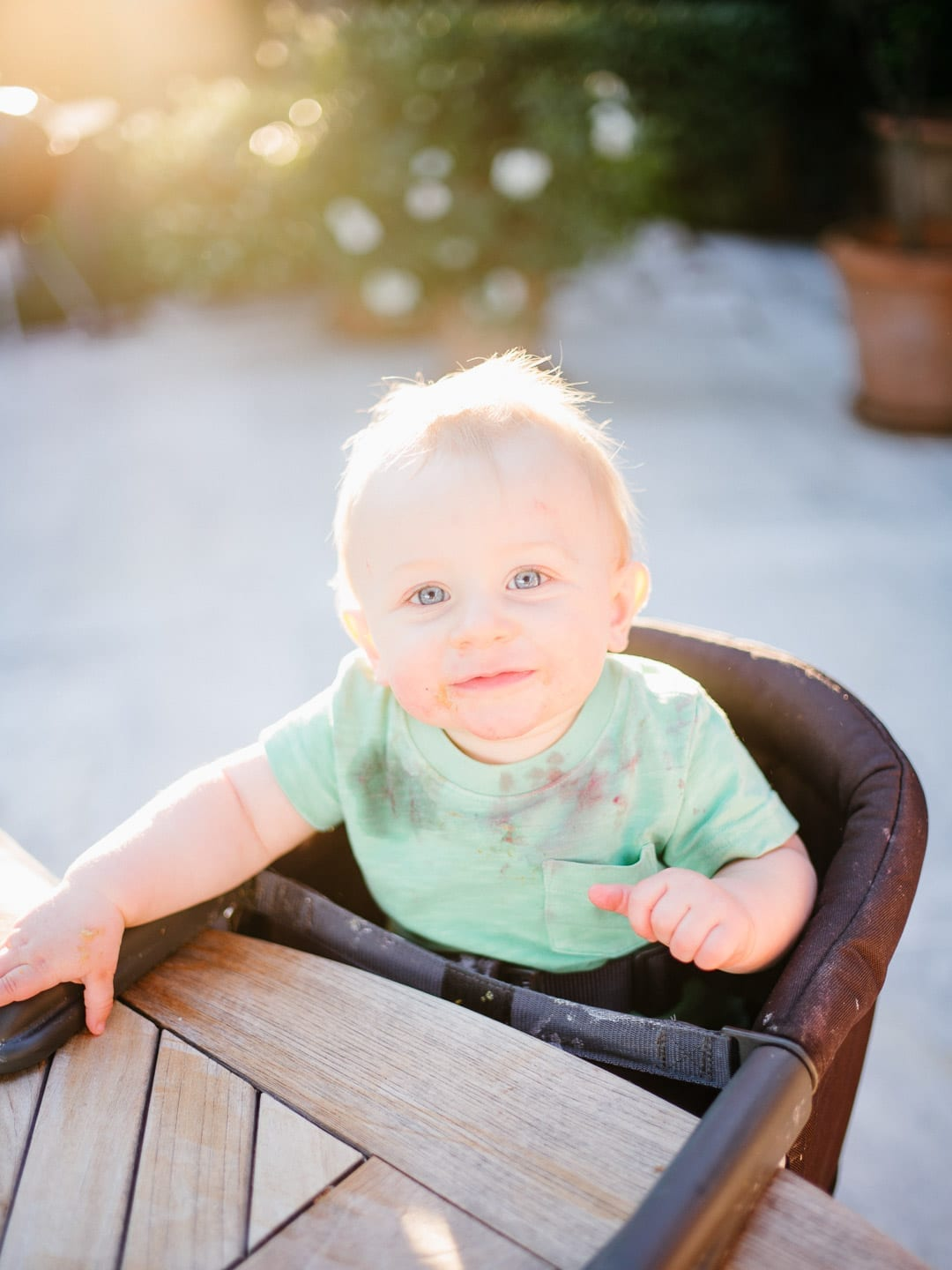 Messy baby sitting in his highchair outdoors - First Glimpse of France