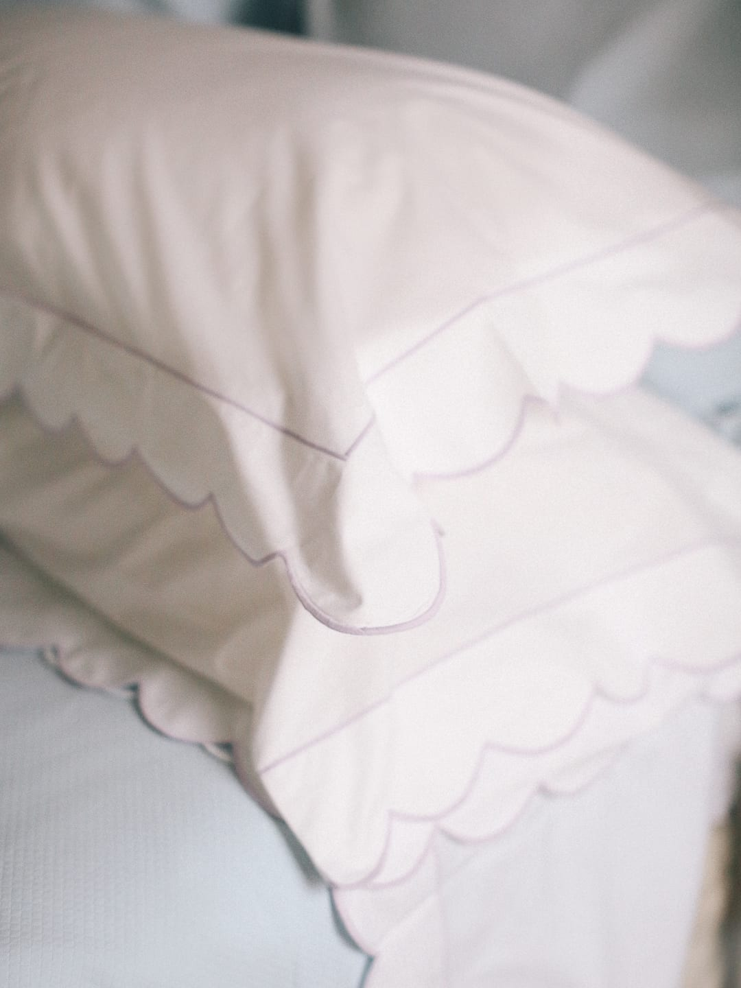Dreamy Bedding with Matouk - White pillows with scalloped edges on a bed