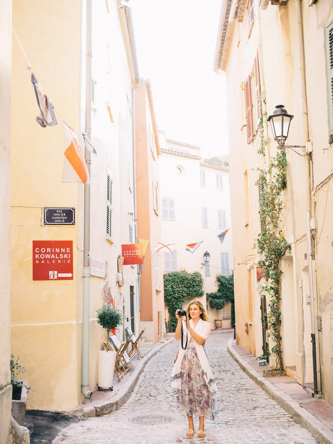 All Our Best Photography Tips & Tricks - Woman photographing historic buildings in France on a cobblestone road