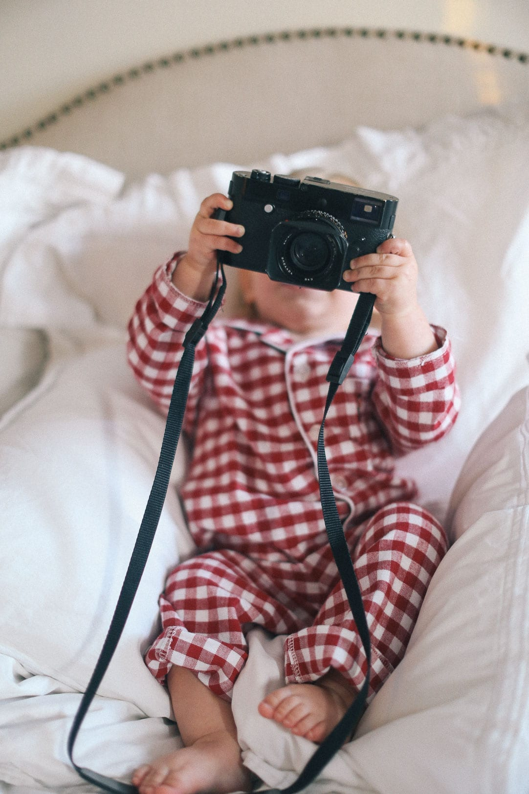 All Our Best Photography Tips & Tricks - baby wearing red checked pajamas holding a Leica camera in bed
